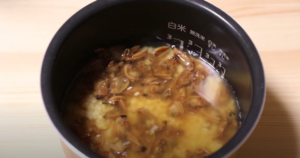 炊飯器にアサリの缶詰たきこみごはんの材料を入れるシーン