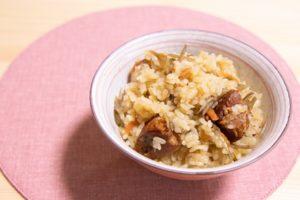 茶碗に入れたセブンイレブンのきんぴらごぼうと豚角煮の炊き込みご飯